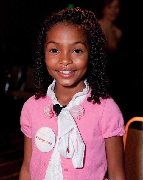 """Yara du haut de ses sept ans portant le badge """"change maker"""" (""""faiseuse de changement"""")"""